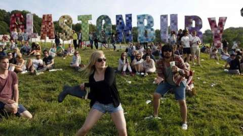 Festival-goers play a game, batting a beer can with a Wellington boot, on the first day of the Glastonbury music festival at Worthy Farm in Somerset, in this June 27, 2013