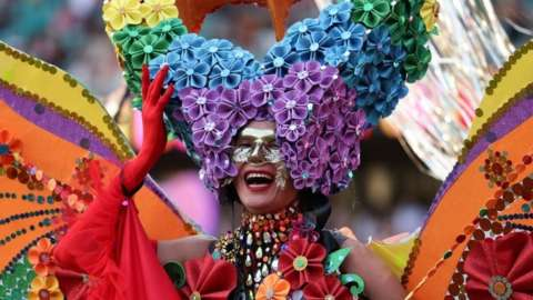 A participant is seen in a huge elaborate rainbow-themed butterfly costume