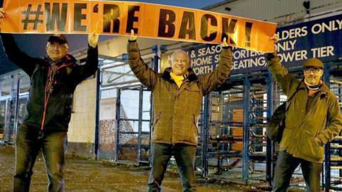 Luton Town fans pose with a banner