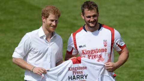 Prince Harry (left) is presented with a rugby league shirt by Sean O'Loughlin (right)