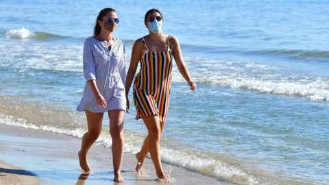 Women walking on a beach in Peñíscola, Spain