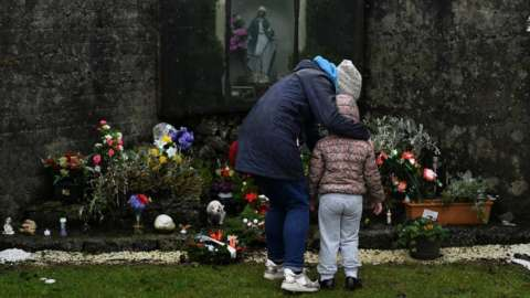 A mother and her daughter pay their respects at the Tuam graveyard where the bodies of 796 babies were uncovered