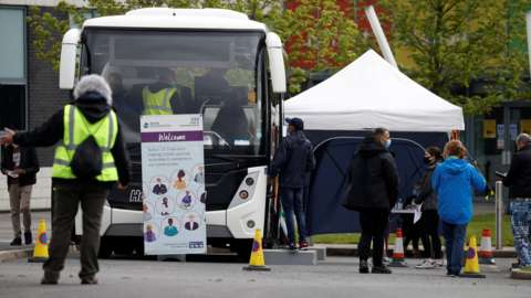 People line up outside a mobile vaccination centre in Bolton on Friday