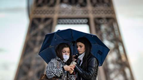 Two girls, one wearing a face mask, check a mobile phone under an umbrella in front of the Eiffel Tower