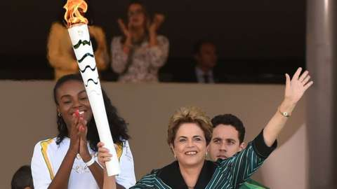 Brazilian volleyball player Fabiana Claudino (L) applauds as Brazilian President Dilma Rousseff holds the Olympic torch at Planalto Palace in Brasilia following the flame's arrival in the country on May 3, 2016
