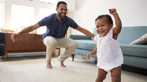 A dad dancing with his toddler daughter