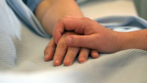 A hospital patient's hand is held by the hand of another person