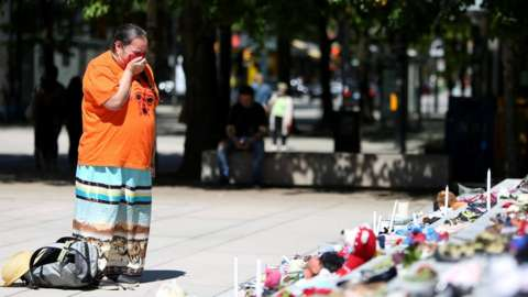 A woman mourns over 215 pairs of children's shoes outside Vancouver Art Gallery.