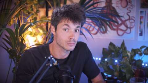 Image of a YouTuber sitting in a dimly lit room with a microphone in front of him and pot plants behind him. He is looking straight at the camera and has his eyebrows raised.