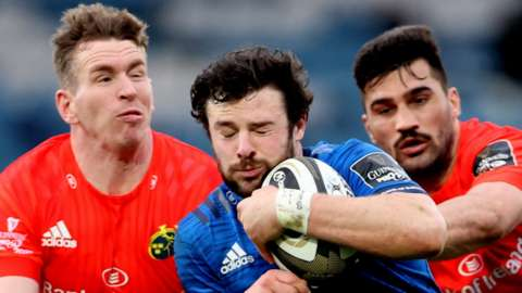Munster's Chris Farrell (left) and Damian de Allen (right) tackle Leinster's Robbie Hensaw