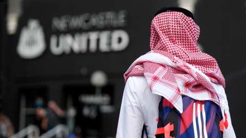 Newcastle fan facing away wearing Saudi headwear in front of Newcastle United sign