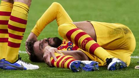 Gerard Pique holds his knee as he awaits treatment on the pitch