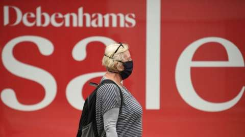 Masked woman in front of Debenhams sale sign