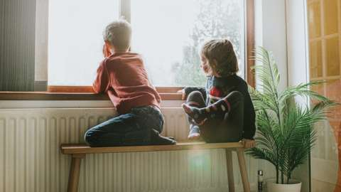 Two children sat by the radiator