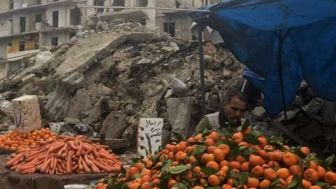 A man pictured at a market stall surrounded by rubble