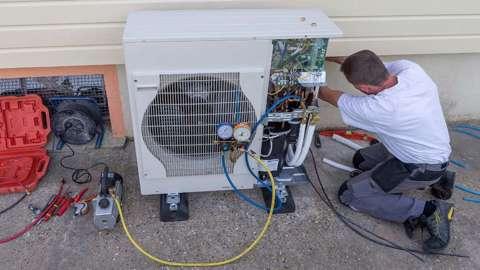 Engineer inspecting heat pump