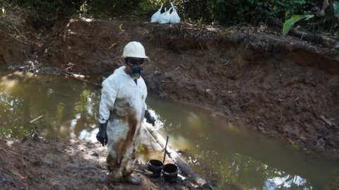 Man cleaning up some of the contaminated soil