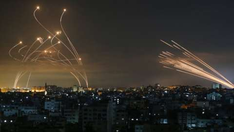 Rockets are seen in the night sky fired towards Israel from Beit Lahiya in the northern Gaza Strip (14 May 2021)