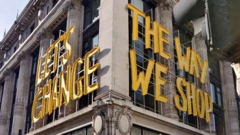 """Let's Change the way we shop"" yellow sign onside of Selfridges building"