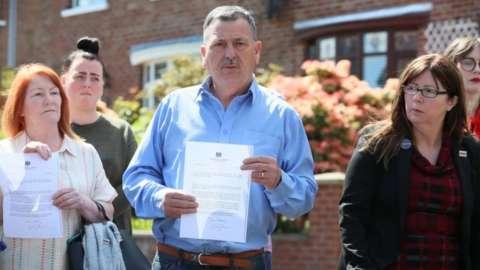 John Teggart and other Ballymurphy families holding Boris Johnson's letter