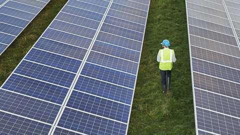 Man walking past solar panels