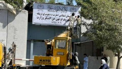 People on a mechanical crane attend to a white signboard outside a building in Kabul