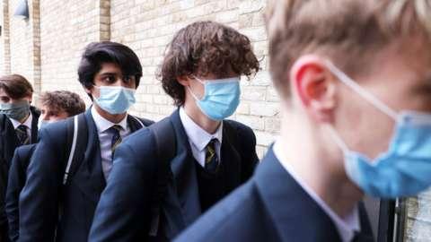 School boys line up wearing masks