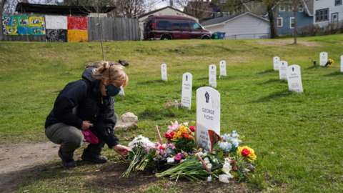 A mourner lays flowers to the grave of George Floyd