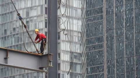 A worker stands on a beam on a construction site in Beijing