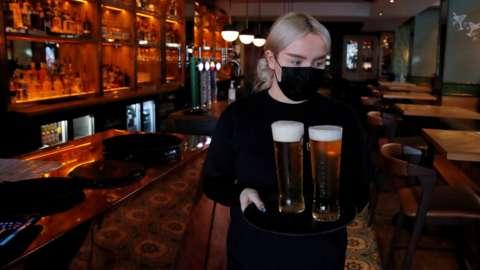 A bar worker serves pints while wearkin a mask