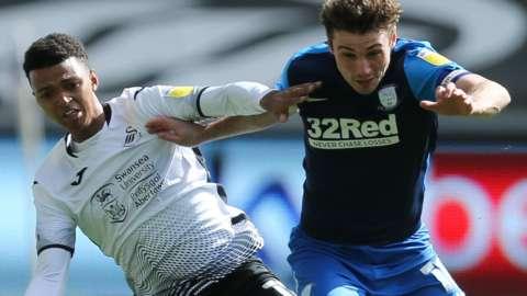 Swansea's Morgan Whittaker (L) challenges Ryan Ledson of Preston