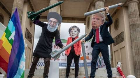 Anti-war activists hold mock nuclear missiles and wear masks of (L-R) Iranian Supreme Leader Ayatollah Ali Khamenei, German Chancellor Angela Merkel and US President Donald J. Trump as they perform in front of the Brandenburg Gate in Berlin,