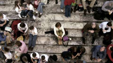A woman sits alone on crowded steps
