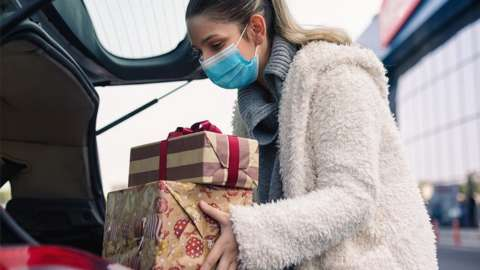 Woman puts presents in a car with a face covering on
