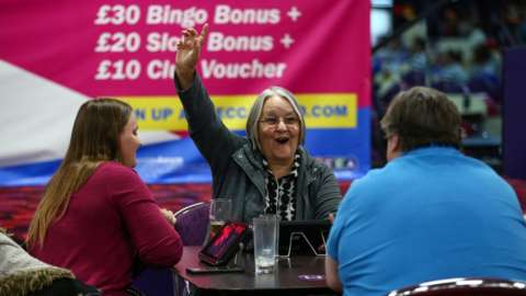 A woman celebrates a win at an indoor bingo hall in July 2020