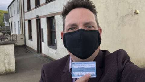 BBC Wales' George Herd holds up vaccine record outside his GP surgery in Gwynedd