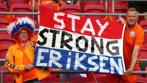 Dutch fans show their support for former Ajax midfielder Christian Eriksen, who collapsed on the pitch playing for Denmark at Euro 2020