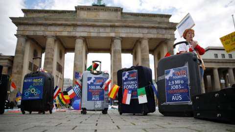 Travel agency workers stand next to suitcases decorated with protest posters as they demonstrate on May 13, 2020 in front of Berlin's landmark the Brandenburg Gat