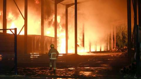 Firefighter in front of industrial estate blaze