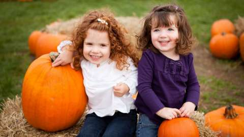 Two young girls in a pumpkin field