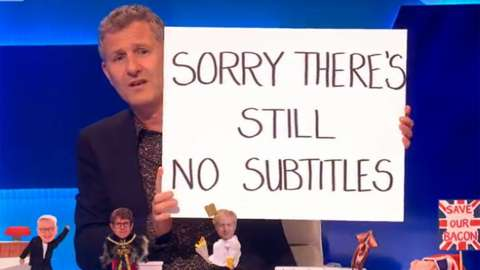 """Adam Hills on Channel 4's The Last Leg holding up a sign reading """"Sorry there's still no subtitles"""""""