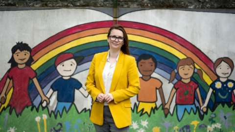 Wales' Education Minister Kirsty Williams poses for a photograph in front of a rainbow mural at Roath Park Primary School on June 29, 2020 in Cardiff