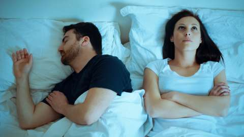 A young woman struggles to sleep, whilst her partner sleeps soundly beside her