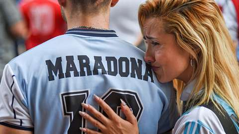 Woman crying on the shoulder of a man wearing a Maradona football jersey