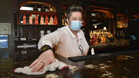 A female bar worker with short hair, wearing a disposable face covering, standing behind a bar and cleaning down the bar counter