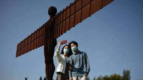 People taking selfies in masks at the Angel of the North