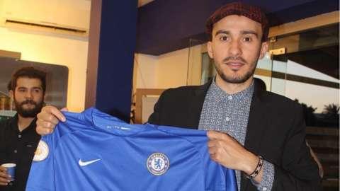 Mohammed Al-Arabi holding a Chelsea shirt