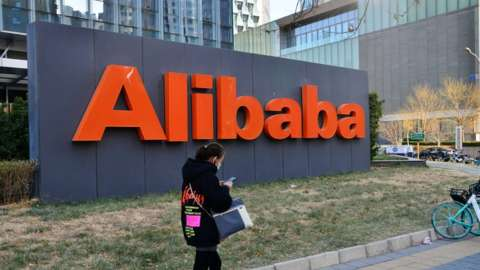 A woman passes an Alibaba office in Beijing, China, 24 December 2020
