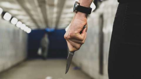 A man holding a knife in a subway