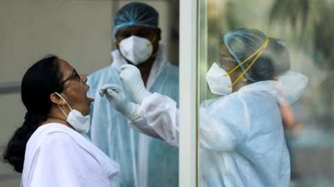 A healthcare worker in personal protective equipment (PPE) collects a swab sample from a woman during a testing campaign for the coronavirus disease (COVID-19), in Navi Mumbai, India